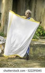 19/10/2016 Kerala, India, old woman working folding sheets at commercial laundry dhobi khana