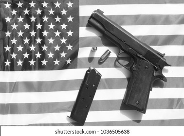 1911 . 45 caliber pistol complete with clip and shells on a American flag. 2nd Amendment Rights to Bear Arms versus Gun Control controversy concepts.  colorized
