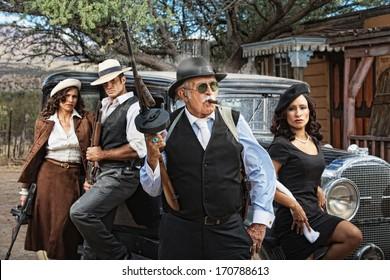 1920s dangerous criminals with guns next to vintage car