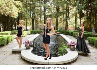1920's fashion shoot - Three stunning young Caucasian women wearing black vintage appearing dresses with headbands standing around an outdoor pond or pool in garden courtyard