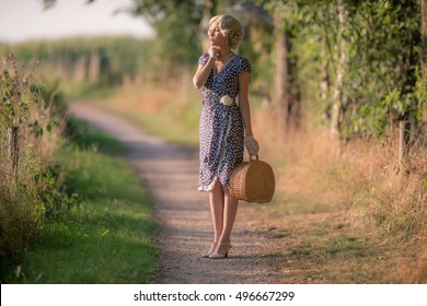 1920s retro fashion woman standing with handbag on rural pathway.