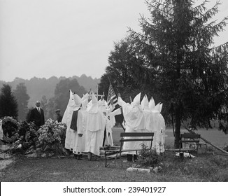 1923 Ku Klux Klan funeral ritual. The KKK offered members regalia, costumes, and rituals with its racism. - Shutterstock ID 239401927