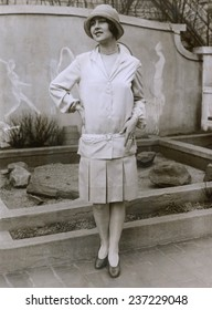 1927 suit with a mid-knee pleated skirt and matching waistless hip-belted jacket The outfit is toped by a cloche hat. March 1927.