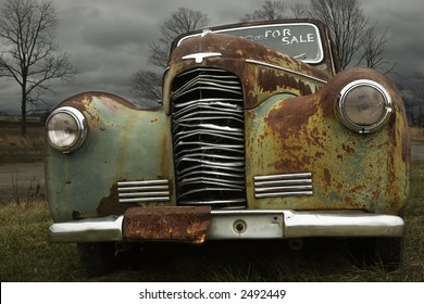 1930's antique car that's rusting in a field hoping to be sold.