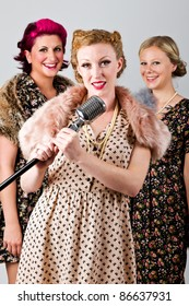 1940's 3 part harmony singing group on a grey background