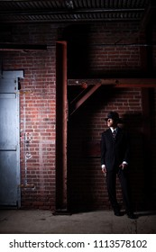 A 1940s style film noir gangster on the lookout in an old abandoned warehouse.
