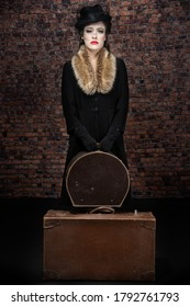 A 1940's woman in a hat, coat and fur collar against a brick wall