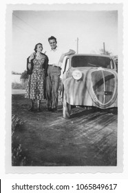 1950 happy young couple and car