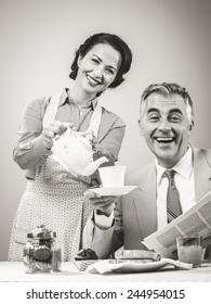1950s beautiful woman serving tea for breakfast to her smiling husband