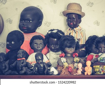 1950s vintage African, Afro-Caribbean and Polynesian dolls collection with clothes and items contemporary to historical periods and cultures displayed on a wooden shelf. Home decor and interior design