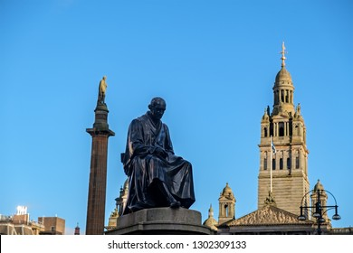 A 19.c. Statue of James Watt (inventor of the steam engine) with the column of Sir Walter Scott and Glasgow City Chambers at the background. Glasgow, Scotland