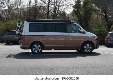 19th April 2021- A bronze and white Volkswagen California Ocean Tdi S-A, large five door family MPV, in the village carpark at Amroth, Pembrokeshire, Wales, UK.
