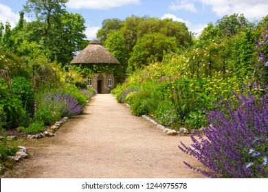 The 19th Century thatched round house surrounded by beautiful flower beds and gravel paths in the walled garden at West Dean Gardens in West Sussex