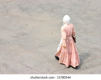 19th century woman walking in a courtyard