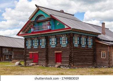 19th century wooden izba house with ornate decoration of the main facade and small balcony above the residential section in Russian northern village Semenkovo