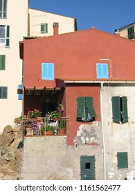 19th of July 2004 - Scene from Il Cotone with close up of red house with blue shutters, Marciana Marina, Elba, Italy