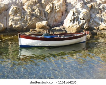 19th of July 2004 - Scene from Il Cotone with close up of small wooden boat against warm cliffs, Marciana Marina, Elba, Italy
