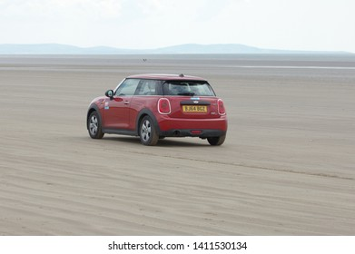 19th May 2019- A red Mini One D saloon car being driven on the sandy beach at Pendine, Carmarthenshire, Wales, UK.