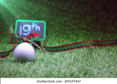 19th sign with Christmas ribbon with  golf ball on green grass