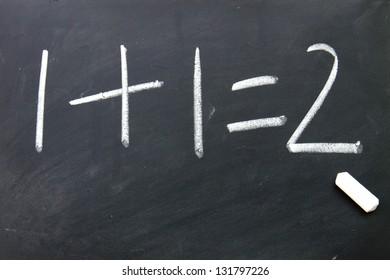 1add 1=2 written with chalk on blackboard