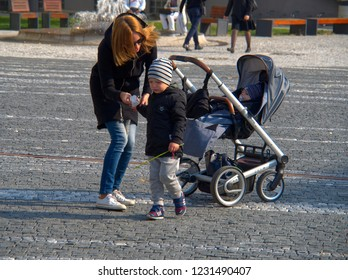 1.October 2018, Trnava, Slovakia Mother wipes to a small son palm with a handkerchief. The second child is lying next to the baby cart.