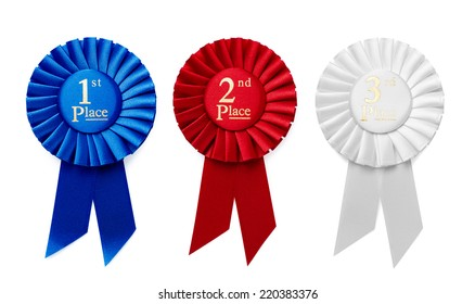 1st, 2nd and 3rd Place pleated ribbon rosettes or badges in blue, red and white respectively with central text isolated in a row on a white background, overhead view