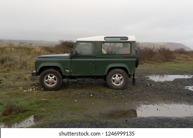 1st December 2018- A classic Land Rover Defender 90 Td5 station wagon in a public parking area on the salt marsh at Ginst Point near Laugharne, Carmarthenshire, Wales, UK.