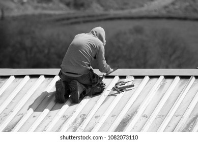 1st May 2018- A man doing some repairs to a sheet metal profile roof at Llansadurnen near Laugharne, Carmarthenshire, Wales, UK.