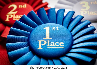 1st place blue winners rosette or badge to be awarded as a prize to the winner of a competition made of pleated blue ribbon with central text in gold with a 2nd place red rosette behind