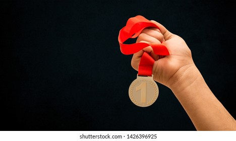 1st position award Ribbon in hand, banner on black background, Success concept