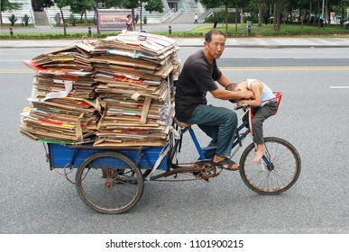 1stof October 2011 - Scene from Chines city with man on a tricycle loaded with cardboard also carrying a sleeping kid, Dongguan, china