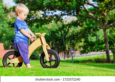 2 - 3 years joyful boy riding a wooden balance bike (run bike). Happy barefoot child learning to wheel, keep balance on training bicycle in the garden. Active kid playing outside. First day on bike.
