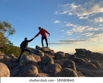 2 adventurous male tourists pulling hands to help each other climb a rock  In a hand holding a trekking stick  On the stone courtyard button at sunset  While the sky is beautiful clouds