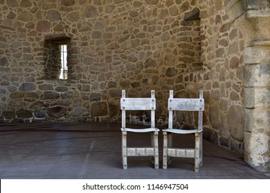 2 ancient chairs on stage in the ruins of a castle