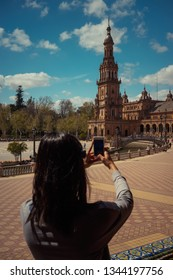 2 apr 2018 Sevilla Spain Plaza de Espana bridge Andalusia. Girl making photo of famous historic touristic place at her travel. Backpack travel concept.