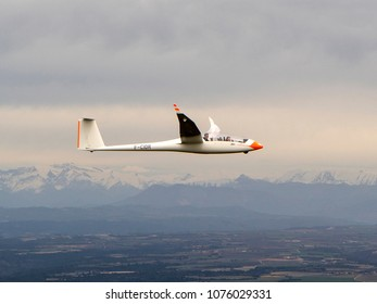 2 April 2018, Vinon, France. Air-to-air aerial view of a Duo Discus glider in the provence. Cloudy weather, mountains with snow on the horizon. Two pilots, a boy and a girl, are smiling and waving.