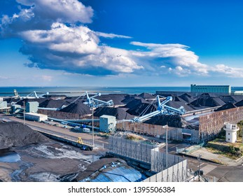 2 April 2019: Yokkaichi Port, Japan - Imported coal and loading equipment at Chubu Coal Centre, on a sunny spring day.