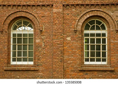 2 arched glass windows set in red brick wall