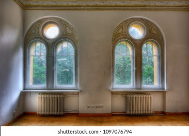 2 arched windows with dirty windows in an abandoned house