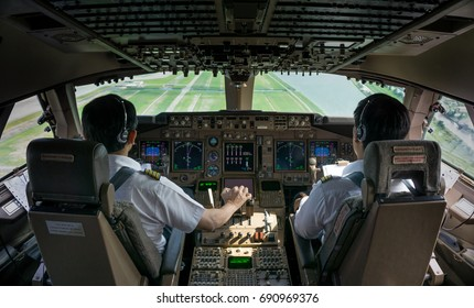 2 Asian Commercial pilots,captain and first officer (co pilot) fly the jet plane in daytime view in cockpit (flight deck) with green field outside as background.