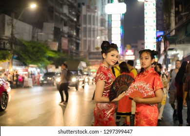 2 Asian women wearing cheongsam dress and holding Chinese fan. They standing at Chinatown, Yaowarat, Bangkok, Thailand. Concept Chinese New Year and Lunar New Year