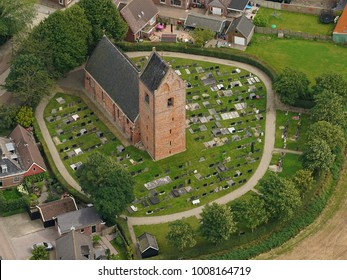 2 August 2017, Oosternijkerk, Holland. Aerial view of the Sint Cecilia kerk in a small village in the province of Friesland. It is a small medieval church with a cemetery in a circle shaped pattern.