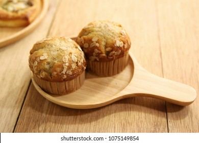 2 banana muffins on wooden plate.