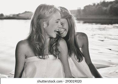 2 beautiful princess young ladies in white dresses on summer water outdoors background, black and white photography