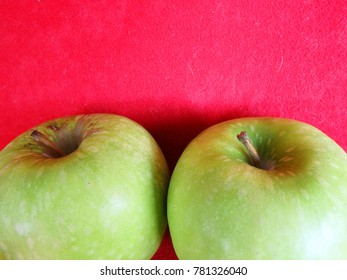 2 big green apples in red background