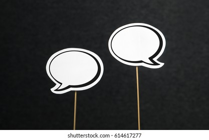 2 blank speech bubbles on a dark black background. Chat bubble cut from paper with wooden stick. Fun discussion, protesting and commenting concept with plenty of free copy space for your own text.