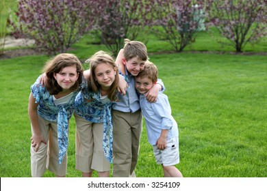 2 boys and 2 girls outside in yard smiling
