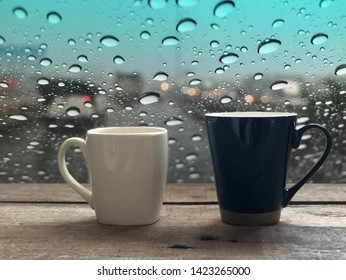 2 Coffee mugs on old wooden planks,with dimly light, in front of window with raindrops,blurred light,traffic on the road in the city,colorful bokeh as outside view.Coffee time in rainy day concept.