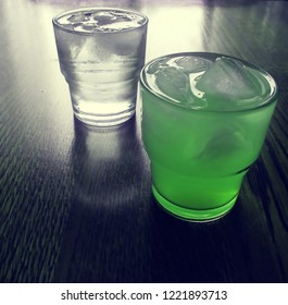 2 cold soda beverages with a lot of ice. The drink in the front got a green color and the drink behind it got a white water color. Both soda drinks are in small glasses. Food and beverage concept.