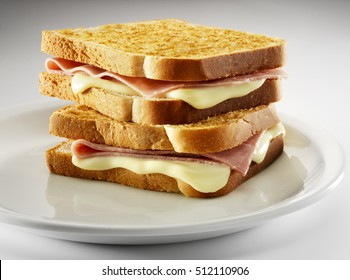 2 croque-monsieur sandwiches piled , on a white plate